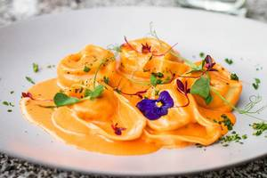 Tortellini with sauce and flowers. Close up