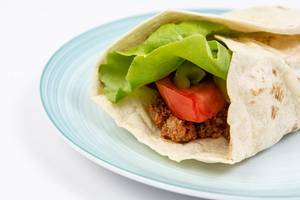Tortilla with Minced meat Tomato Lettuce served on the plate