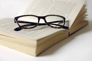Tortoise shell glasses on an open book on white background