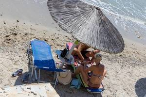 Tourist couple under a straw parasol at the beach