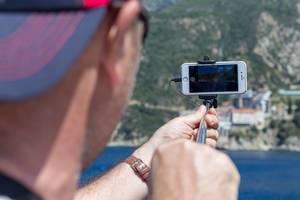 Tourist fotografiert das Kloster Moni Osiou Grigoriou mit seinem Handy