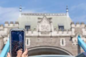 Tourist fotografiert die Tower Bridge mit dem Handy