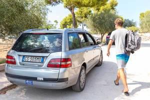 Tourist im Sommerurlaub geht auf ein Mietwagen zu