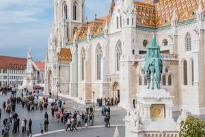 Touristen auf dem Platz vor der weißen Matthiaskirche in Ungarns Hauptstadt Budapest