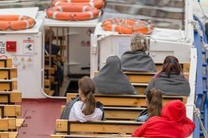 Touristen auf einem Sightseeing-Boot auf der Moika in Sankt Petersburg