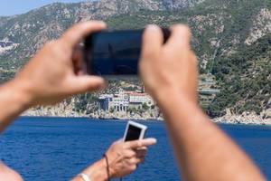 Touristen fotografieren Kloster Moni Osiou Grigoriou mit ihren Handys