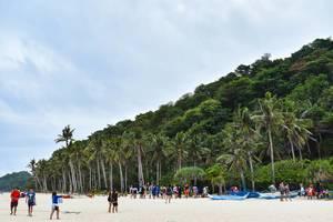 Touristen genießen den paradiesischen Puka Beach auf Boracay mit schneeweißem Sand und Palmen