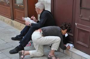 Touristen schauen sich die Stadtkarte von Wien an und schreiben Ansichtskarten