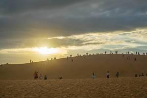 Touristen sehen sich den Sonnenuntergang über Mui Ne, Vietnam von den roten Sanddünen aus an