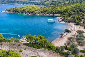 Touristenboot fährt in die Bucht des Paralia Zogeria Strandes auf der Insel Spetses, Griechenland