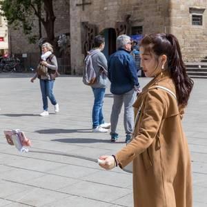 Touristin mit Selfiestange am Plaça Nova nahe der Kathedrale La Seu in der Altstadt von Barcelona, Spanien