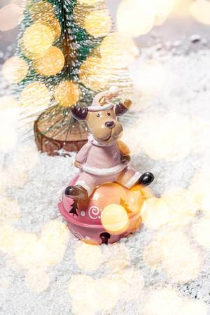 Toy deer on white snow with Christmas tree and Golden bokeh background (Flip 2019)