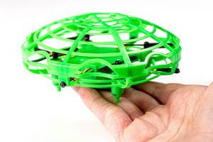 Toy green flying drone in a hand (Flip 2020)