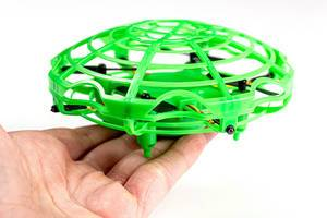 Toy green flying drone in a hand