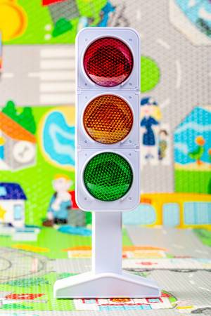 Toy model of traffic light with the image of the road in the background