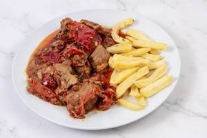 Traditinal meal Muckalica with Pork Meat and French Fries (Flip 2019)