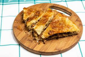 Traditional balkan burek pie with meat sliced and served on wooden board