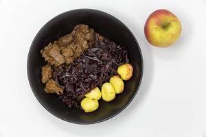 Traditional beef stew with apple beetroot salad and potato dumplings - top view