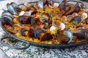 Traditional spanish paella with fresh mussels in a cast iron pan