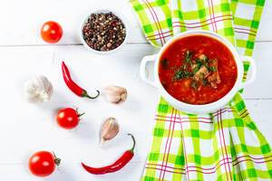 Traditional Ukrainian and Russian soup borsch with spices on a white wooden table