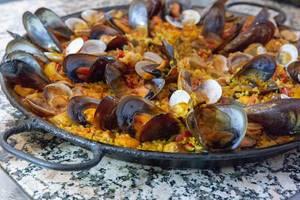 Traditionelle spanische Paella mit frischen Muscheln in einer gusseisernen Pfanne