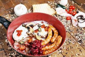 Traditionelles Englisches Frühstück in einer Bratpfanne auf einem Holztisch
