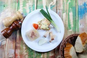 Traditionelles Frühstuck aus der Balkanküche mit Schweinefleisch in Aspik und Speck vor einem Retro-Hintergrund