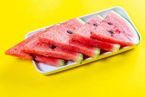 Triangular pieces of ripe red watermelon on a yellow background (Flip 2019)