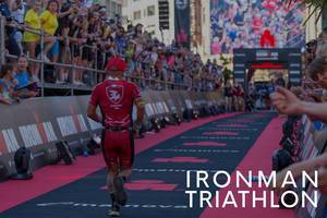 Triathlete runs the last meters of the marathon during the Ironman Triathlon, with thunderous applause from spectators