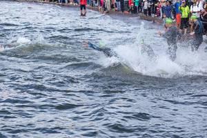 Triathleten bei der Ironman-Sportart Schwimmen im Süden von Finnland am Vesijärvisee, spritzen beim Sprung ins Wasser