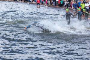 Triathletes start the Ironman swimming competition in the south of Finland at Lake Vesijärvisee and jump into the water