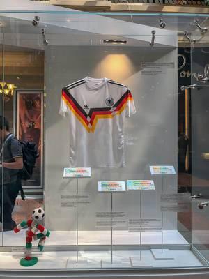 Trikot der deutschen Nationalmannschaft bei der Fußball-Weltmeisterschaft 1990 in Italien und das Maskottchen Ciao