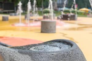 Trinkbrunnen am Spielplatz, Fontäne im Hintergrund