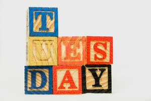 Tuesday text on wooden blocks on white background