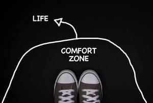 Turnschuhe stehen auf schwarzem Hintergrund und verlassen die Comfort Zone, um ins Leben zu starten