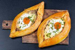 Two baked Adjarian khachapuri on a wooden kitchen board, top view