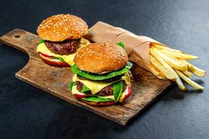 Two burgers and fries on an old kitchen Board (Flip 2019)