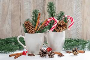 Two cups with lollipops, cones and branches of the Christmas tree. Festive winter background (Flip 2019)