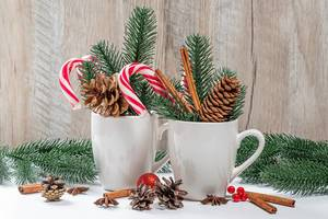 Two cups with lollipops, cones and branches of the Christmas tree. Festive winter background