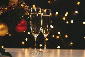 Two glasses of champagne and Christmas tree on a blurry background of a luminous garland (Flip 2019)