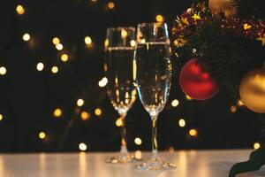 Two glasses of champagne and Christmas tree on a blurry background of a luminous garland