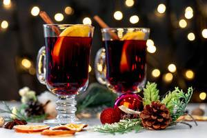 Two glasses of mulled wine with christmas decor and glowing garland background (Flip 2019)