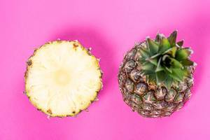 Two halves of a ripe pineapple on a pink background (Flip 2019)