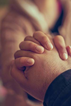 Two hands together, a man and woman holding hands. Husband and wife together. Support, loving, caring and understanding concepts (Flip 2020)