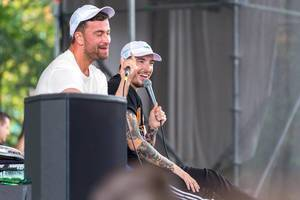 Two happy German Rapper Marteria and Casper on a spontaneous concert sitting on stage