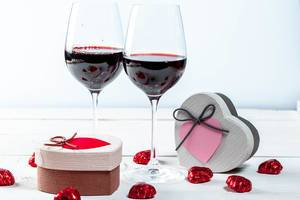 Two Heart Shaped Boxes with Pralines and Two Wine Glasses with Red Wine in the Background for Valentines Day