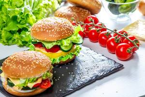 Two homemade hamburgers with fresh vegetables on black stone tray (Flip 2019)