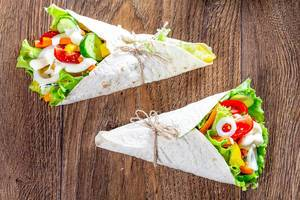 Two lavash cone with vegetable filling on wooden background (Flip 2019)
