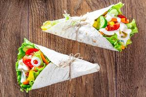 Two lavash cone with vegetable filling on wooden background