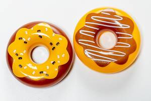 Two plastic donuts toys on white background. Top view (Flip 2019)